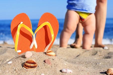 Photo pour Orange flip-flops in sand on the beach in Barcelona  - image libre de droit