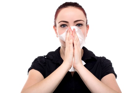 Attractive young businesswoman blowing her nose on her handkerchief after contracting seasonal flu, isolated on white