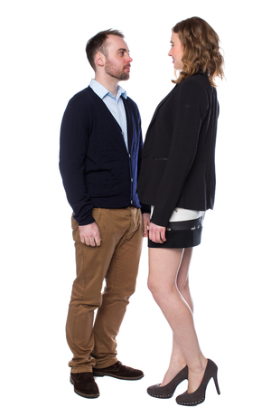 Tall woman confronting a shorter man stepping right up to him and towering over him in a dominant manner, isolated on white