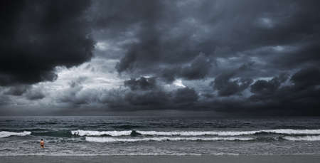 Stormy ocean. A boy is going to swim. Panoramic shot.