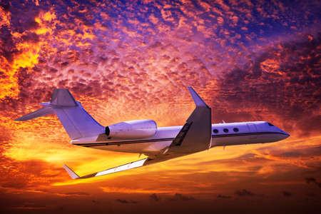 Private jet cruising in a sunset sky