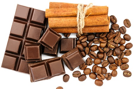 Dark chocolate bar, cubes, cinnamon sticks and coffee beans isolated on white background, top view