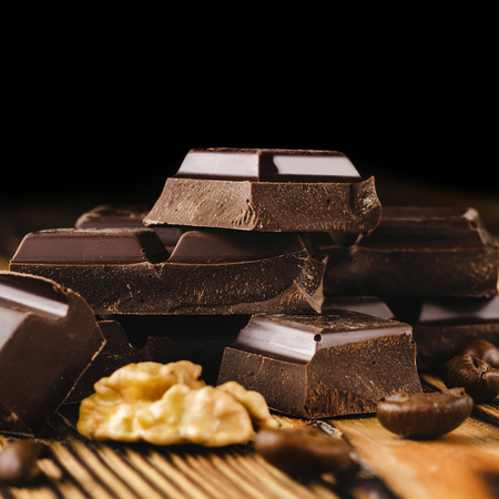 Pieces of bitter, dark chocolate, cubes on heap, walnut core and coffee bean on wooden background, close-up view.