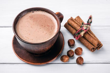 Photo for Hot cocoa with milk in brown clay cup, hazelnut and cinnamon sticks on table of white wooden planks. - Royalty Free Image