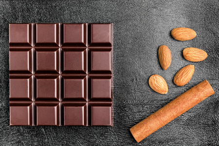 Dark, bitter chocolate bar, almond nuts and cinnamon stick on black leather texture background, top view.