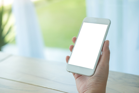 Photo pour Mockup image of hand holding white mobile phone with blank screen on table in cafe - image libre de droit