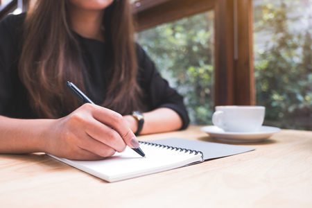 Photo pour Closeup image of a woman's hand writing down on a white blank notebook with coffee cup on wooden table - image libre de droit