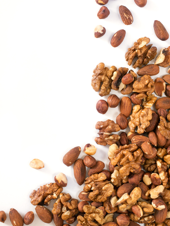 Photo pour Background of mixed nuts - hazelnuts, walnuts, almonds - with copy space. Isolated one edge. Top view or flat lay. Vertical image - image libre de droit
