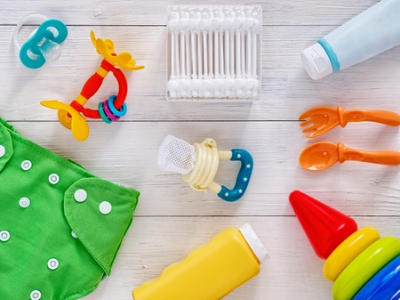 Foto de Collection of items for babies: cloth diaper, baby powder, nibbler, cream, teether, soother, cotton swabs, baby spoon and fork, pyramid toy on white wooden background. Top view or flat lay - Imagen libre de derechos