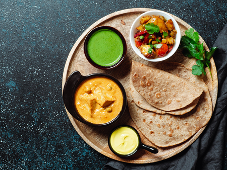 Photo pour Indian cuisine dishes: vegetable curry, shahi paneer, chapati, chutney. Indian food on wooden tray over dark background. Assortment indian meal with copy space for text. Top view or flat lay. - image libre de droit