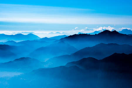 Photo pour the peaks of the Alps around Lake Garda surrounded by fog with blue sky seen from Monte Altissimo, Trento, Italy - image libre de droit