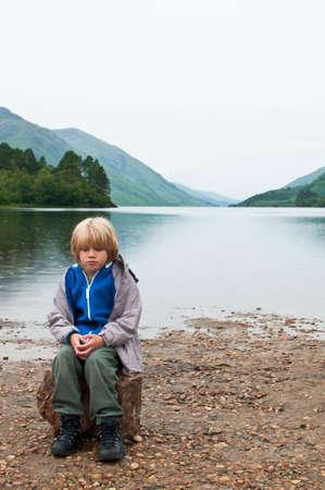 Sad boy by lake