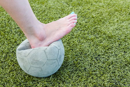 Girl Barefoot and old soccer ball background