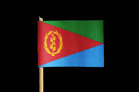 A national and official flag of Eritrea on toothpick on black background. A three triangles which one is red with coat of arms and second is the upper is green and lower is blue.