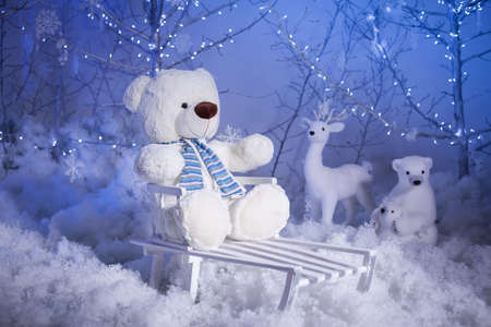 Christmas scene. Polar Teddy bear on a sled. There are winter toys, snowflakes and New Year lights at the background. Holiday decoration