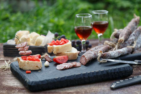 Cured dry sausage with wine, bread and tomato.