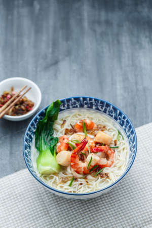 Hawker food bee hoon soup in traditional bowl, copy space