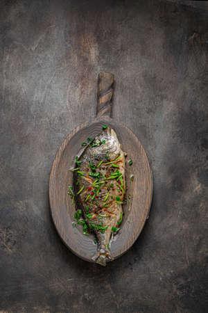 Photo pour Sea bream fish with vegetables on cutting board, copy space. - image libre de droit