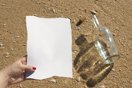 Woman reads the message found in a bottle at the beach (Write your own text)