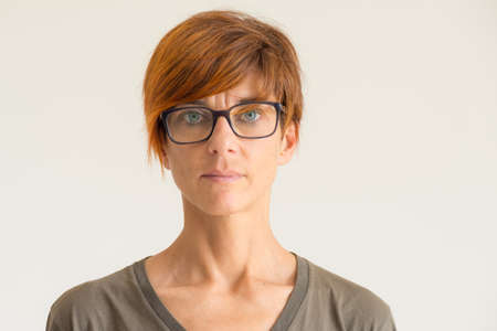 Waist up portrait of mature woman with red hairs, green eyes, eye glasses and serious facial expression, standing against the wall. Natural soft daylight, natural skin, neutral background.