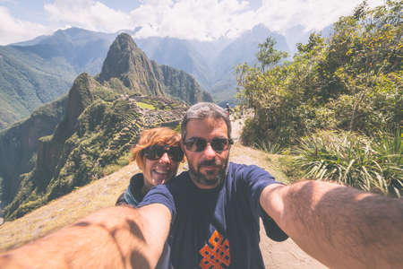 Couple taking selfie on the terraces above Machu Picchu, the most visited travel destination in Peru. Adventures in South America, marsala toned image.