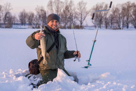 Foto de Winter fishing concept. Fisherman in action with trophy in hand. Catching pike fish from snowy ice at lake. - Imagen libre de derechos