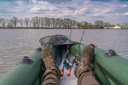 Photo pour Kayak fishing at lake. Legs of fisherman on inflatable boat with fishing tackle. - image libre de droit