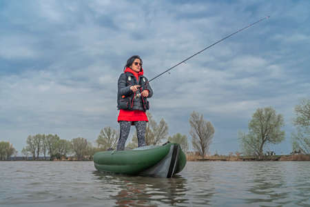 Photo pour Kayak fishing at lake. Fisherwoman on inflatable boat with fishing tackle. - image libre de droit