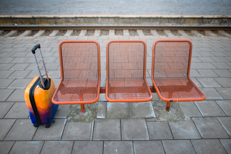 Colorful luggage near the bench. Railway station.