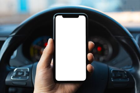 Photo pour Close-up of male hand holding smartphone with white mockup on screen, background of car steering wheel. - image libre de droit