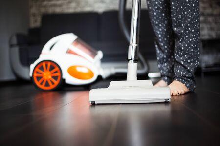 Photo pour Young girl using vacuum cleaner for dark laminate. - image libre de droit