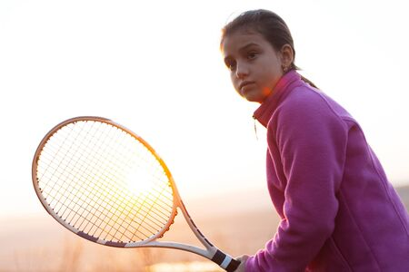 Photo pour Portrait of teenage girl is training tennis skill outside court, in field at sunset. Wearing pink sweater and holding tennis racket. - image libre de droit