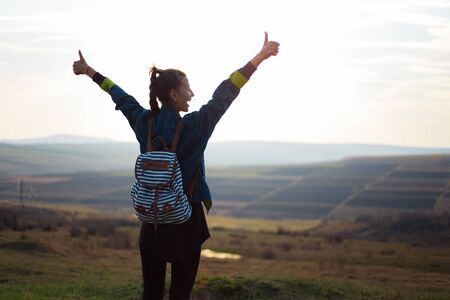 Photo for Back view portrait of young girl, showing thumbs up, wearing denim jacket with backpack, on background of sunset and fields. - Royalty Free Image