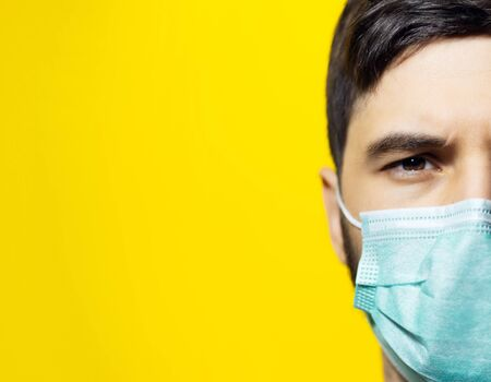 Photo pour Close-up portrait of male face, wearing medical flu mask on background of yellow color with copy space. - image libre de droit