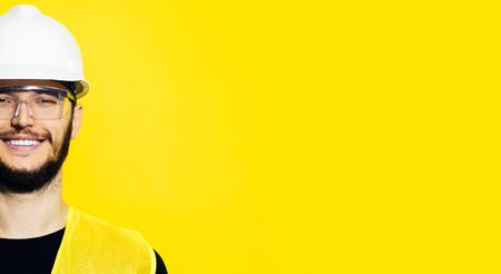 Photo pour Studio half face portrait of young smiling construction engineer worker man, wearing safety helmet and goggles on background of yellow color with copy space. - image libre de droit