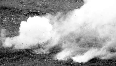 white smoke after a strong explosion of a bomb on a lawn