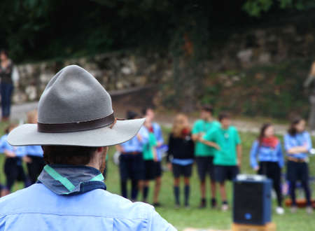 Chief scout with the typical large Hat while controlling their kids to camp