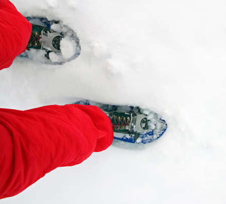 blue snow shoes for walking on soft snow mountain high with red snow suit