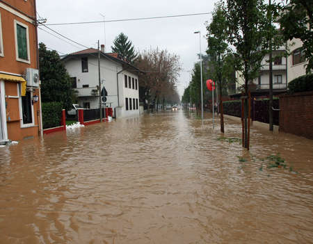 mud River invades the road completely submerged during the flood in the city