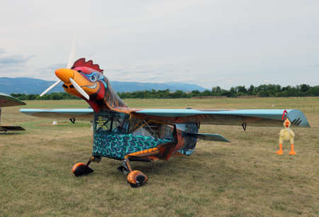 Thiene, Vicenza - Italy. 26th July, 2015: important air show called FlighThiene in Thiene Airport near Vicenza City in Northen Italy with many historical and modern airplanes. Amazing fun hen airplane with head and feathers drawn