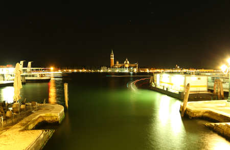 Venice, VE - Italy. 10th July, 2015:  water bus stop with a vaporetto and the church of Saint George at night