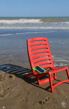 chair on the beach by the ocean wave and a smartphone