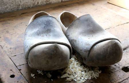 two ancient wooden clogs in the workshop of a shoemaker
