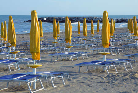Yellow closed Sun umbrellas with sun loungers and deckchairs