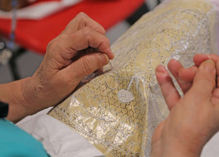 hands of the old woman while embroidering a lace with lace pillow near venice in italy