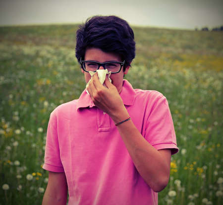 Allergic boy with glasses and pink t-shirt blows his nose using a white handkerchief in springtime