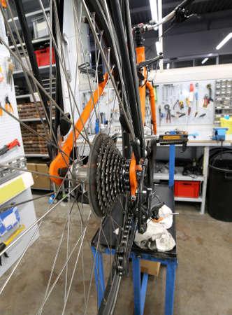 Detail of transmission of broken orange bicycle in the repair workshop