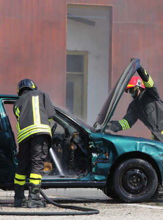 two Firefighters check the incident car after the car accident