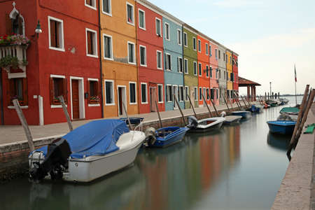 navigable canal and the colorful houses of the BURANO island near Venice with moving boats due to the long exposure time