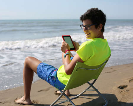 young smiling caucasian boy reads an ebook sitting on the beach chair at the seashore in summer